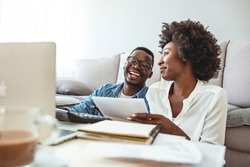 Young married couple doing their paperwork together, paying bills online. Focus on the guy. Loving young couple using laptop and analyzing their finances. Writing notes.