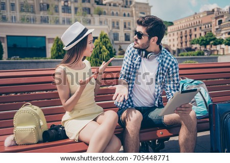Young married couple got lost on vacation in town. Frustrated lady is arguing with her boyfriend, who holds pda, has no idea where they are