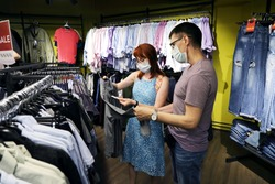 Young married couple wearing medical face masks are choosing clothes in the store. A new reality with health care