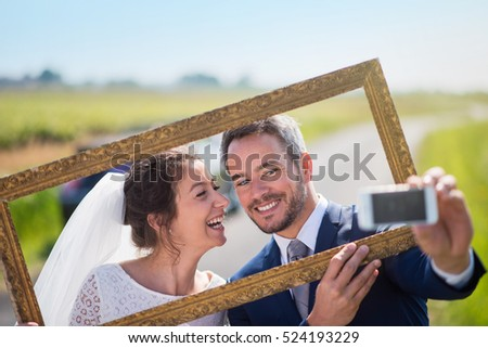 young married couples having fun to take pictures of themselves through an empty frame. this is the husband who holds his mobile and takes a selfie.they are on a country road