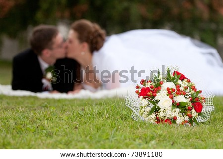 Young marrieds behind a wedding bouquet