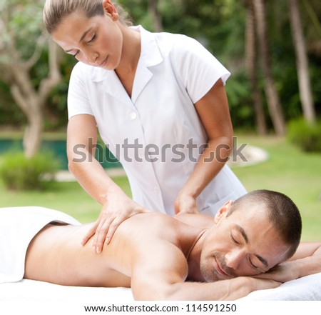 Young masseuse massaging an attractive man in a tropical hotel garden near a swimming pool.
