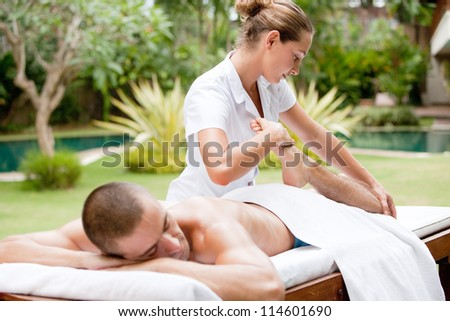 Young masseuse massaging and stretching the body of an attractive man in a tropical hotel garden near a swimming pool.