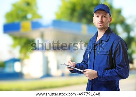 Young mechanic in uniform with a clipboard and pen on gas station blurred background #497791648