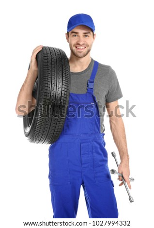 Young mechanic in uniform with car tire on white background #1027994332