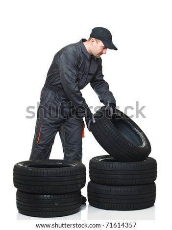 young mechanic move tires isolated on white background