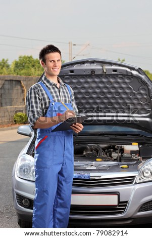 Young mechanic with a clipboard standing next to a car with open hood