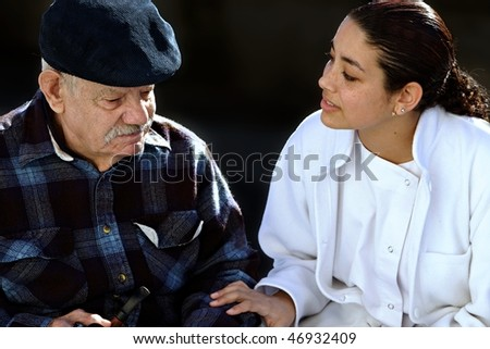 young medical personel helping an old man