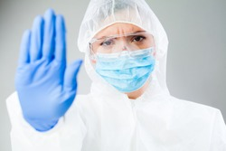 Young medical worker hand gesturing STOP, Coronavirus COVID-19 disease global pandemic outbreak,keep social physical distance,do not enter. Quarantine isolation, safety measures against virus spread.