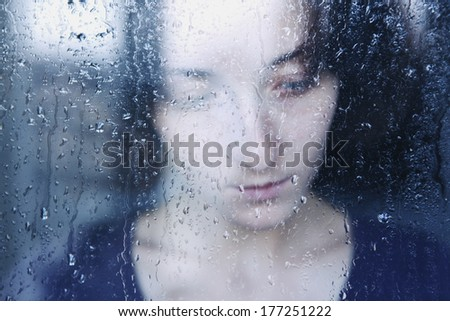 young melancholy and sad woman portrait  behind the window in the rain with rain drops on it