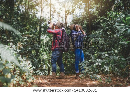 Young men and women and mountain climbing who use binoculars and cameras to enjoy traveling