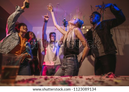 Young men and women having fun at a colorful house party. Friends dancing in joy holding drinks at a house party.