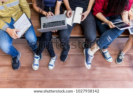 Young men and women sitting relaxed use tablet ,computer notebook on a wooden bench in college.Students using technology to learn the lessons of the student group during semester.summer school camp