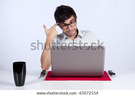 Young men at dinner table eating technology with a suicide gesture while working with his laptop