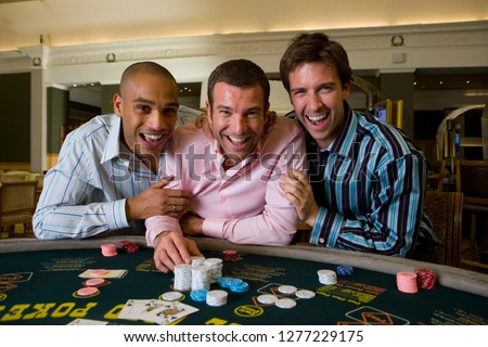 Young Men at roulette table in casino holding gambling chip at camera