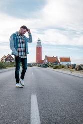 young men at the lighthouse of Texel Netherlands, mid age man on vacation Texel Holland
