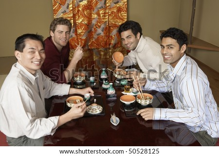 Young men eating sushi with chopsticks in restaurant