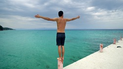 Young men having speech standing on victory hands open post at pier on empty beach with turquoise water
