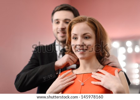 Young men in full suit helping to put on the necklace on his girlfriend