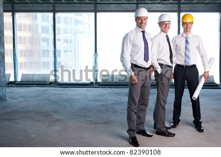 Young men in shirts and helmets on a construction site