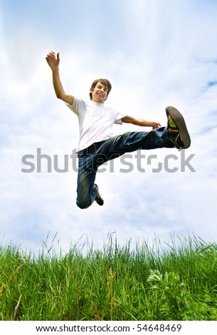 Young men jump in the meadow