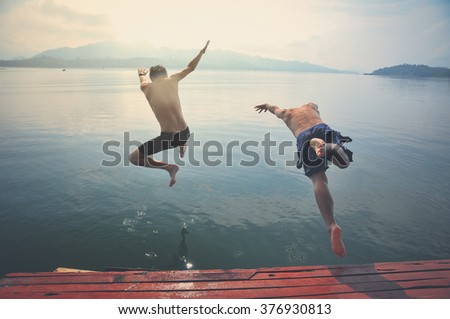 Young men jumping into lake retro image processed.