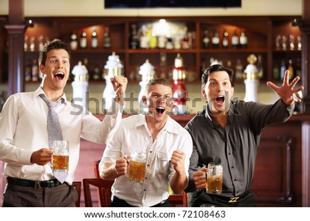 Young men rejoice the victory of his team in a bar - stock photo
