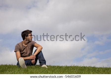Young men sited on the grass looking away