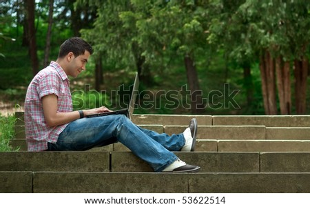 Young men sitting on stairway and using lap-top