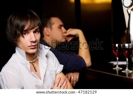 Young men sitting on the bar counter.