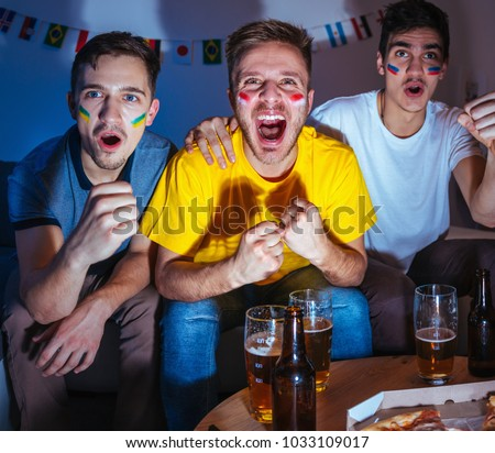 Young men watching football match at home, exited and focused on the game, celebrating and shouting  #1033109017