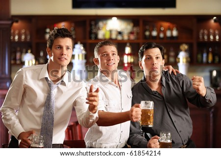 Young men with a beer watching the match in the bar