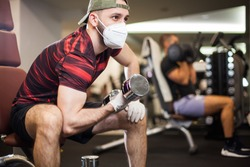 Young men working out wearing face mask & latex rubber gloves,performing bicep curl with dumbbells,COVID-19 pandemic social distancing rules while working out in reopened indoor gym,prevent & protect