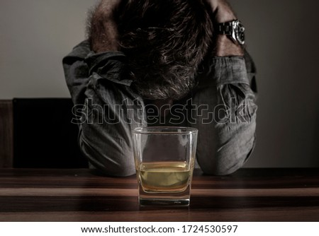 young messy and drunk alcohol addict man drinking whiskey glass at home sitting thoughtful and depressed as alcoholic suffering alcoholism problem and addiction intoxicated and lost ストックフォト ©