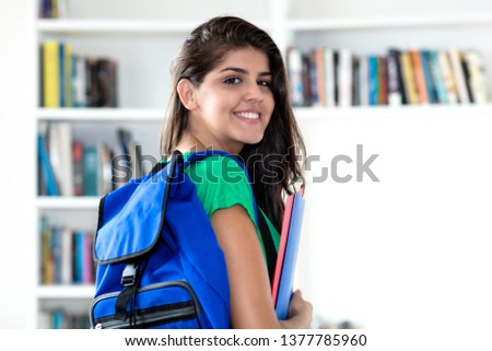 Young mexican female student at library of university