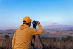 Young Mexican professional photographer with a camera capturing the beautiful landscape