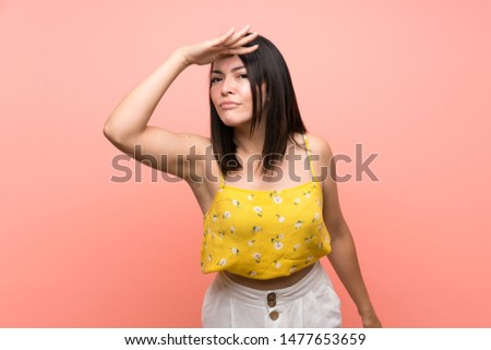 Young Mexican woman over isolated wall looking far away with hand to look something