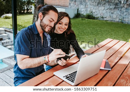 young mexican woman working on laptop while latin man sitting near her in the rest area, Students in Latin America Stok fotoğraf ©