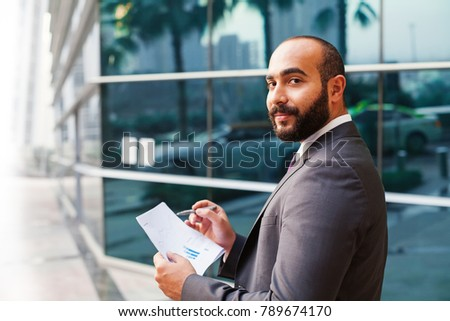 Young middle eastern businessman holding statistics report confidently looking at camera