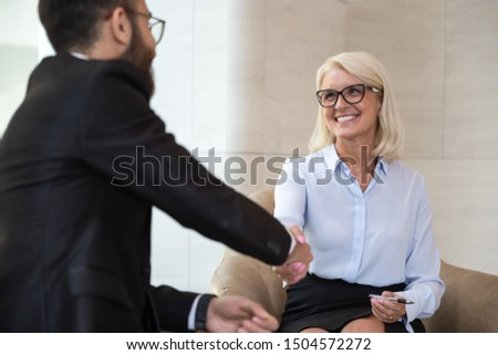 Young middle eastern ethnicity business partner shake hands greet 60s european businesswoman focus on blond attractive smiling businesslady, people starting business meeting or job interview concept