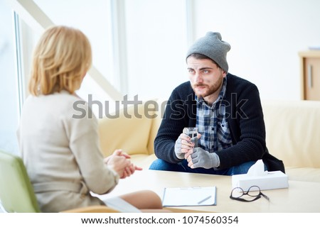 Young migrant or victim of terrorism with glass of water listening to advice of social worker in center of support
