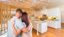 Young Military Couple Facing House Construction Framing Gradating Into Finished Kitchen Build.