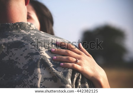 Young military couple kissing in park showing engagement ring