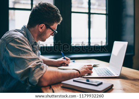 Young millennial male student searching information for homework using laptop and wifi connection indoors, man writing article in textbook for add interesting content on own website or web page