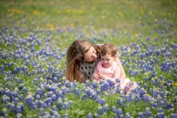 Young Millennial Mother With Daughter During Spring in a Field of Blue Bonnets