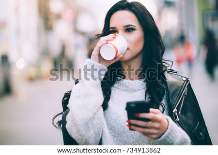 Young millennial woman drinking coffee on street texting