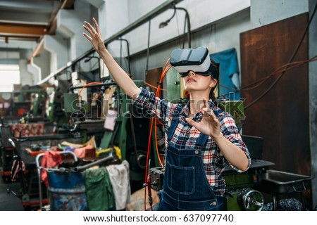 young milling machine female staff through 3D virtual reality devices watching factory working progress and organize content in air through hands at machine workshop.