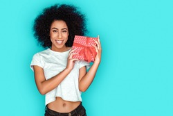 Young mix race girl standing isolated on blue wall holding gift box looking camera smiling playful
