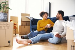 Young mixed ethnicity couple taking a break on moving day into new home sitting on floor in lounge drinking coffee surrounded by removal boxes