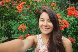 Young mixed race  asian girl with long black hair takes selfie smiling, portrait with flowers